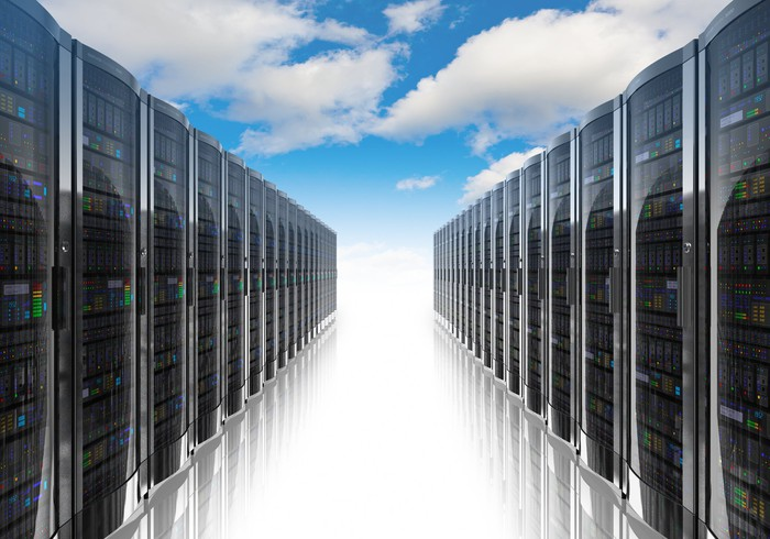 Rows of server racks, as in a modern data center, but under a blue sky with fluffy white clouds.