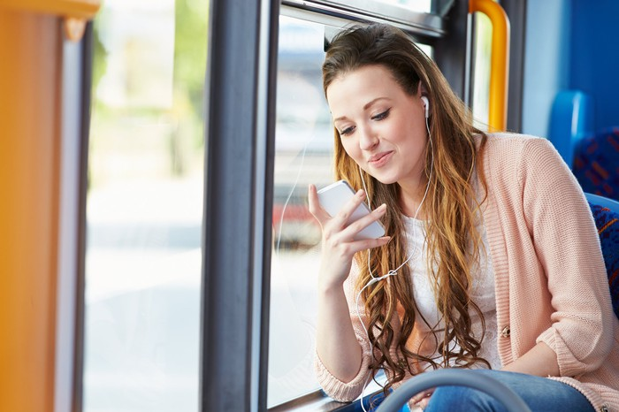 Young woman on a bus, smiling at her smartphone while wearing headphones.