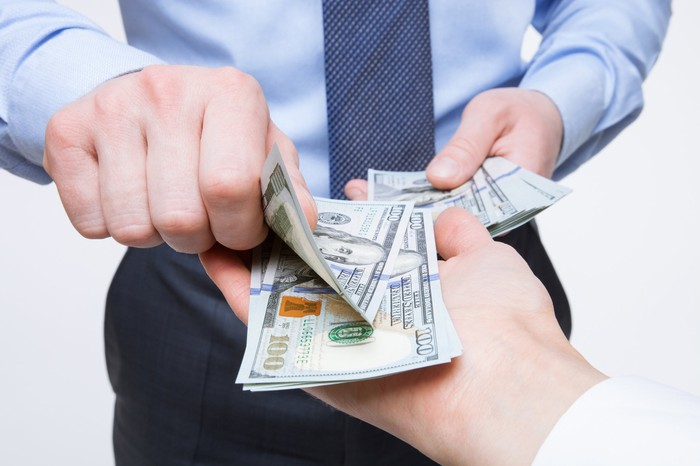 Businessman putting $100 bills into another person's hand