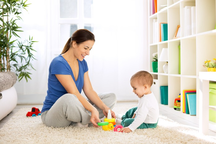 Woman and baby playing on the floor