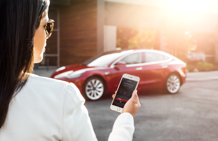 A woman unlocks her red Model 3 with a Tesla app on her smartphone.