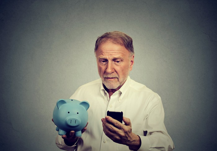Older man holding a blue piggy bank and looking at a phone