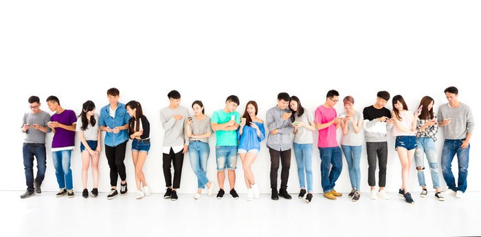 Wide angle shot of 17 male and female young Asians standing against a white background and looking at mobile devices.