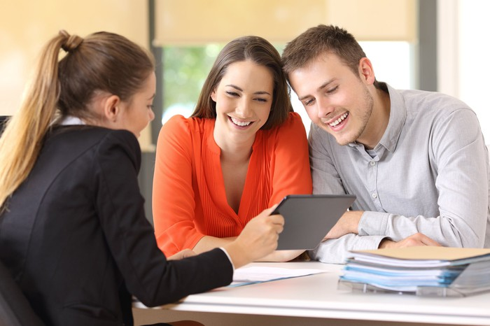 A smiling young couple closing the deal on a new home, with a female realtor and a large folder of paperwork on the table in front of them.