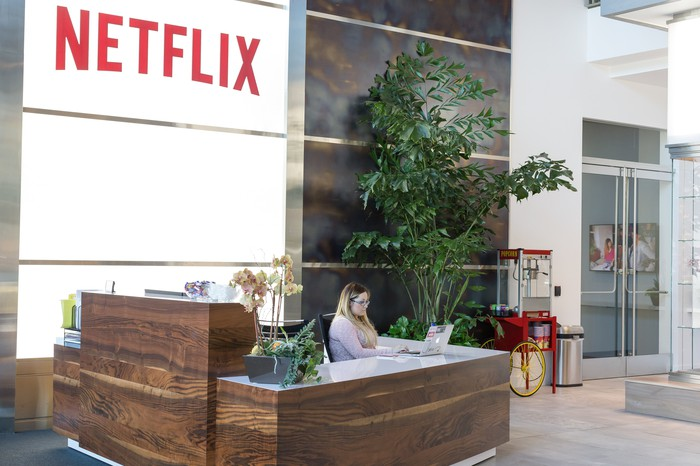 A person sitting behind a desk looking at a laptop in the lobby of Netflix's office in Los Gatos, California.