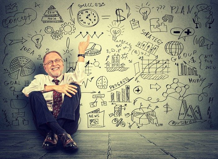A man in dress clothes sitting on a floor smiling while pointing at a clock drawn on a wall full of diagrams.
