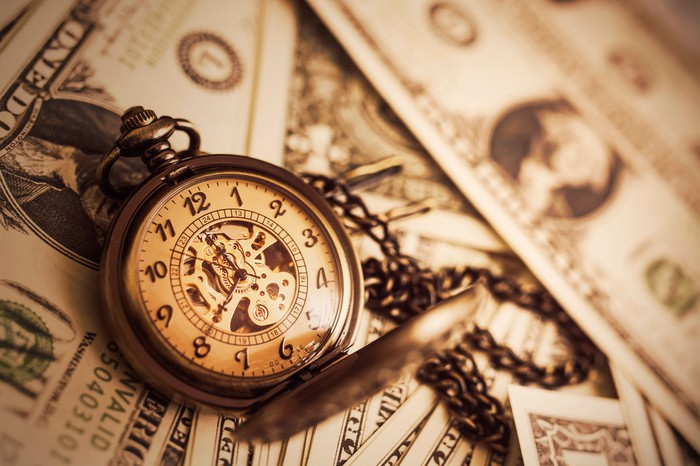 Traditional pocket watch on a chain sitting on top of paper currency