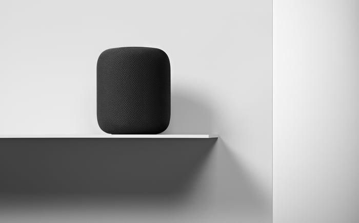 A black HomePod on a shelf