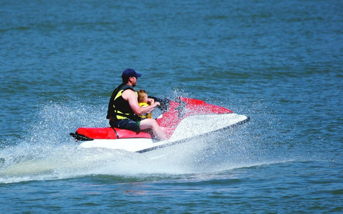 A father and his son on a jet ski in the ocean.