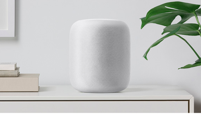 A white Apple HomePod sits on a white table with a white wall behind it.