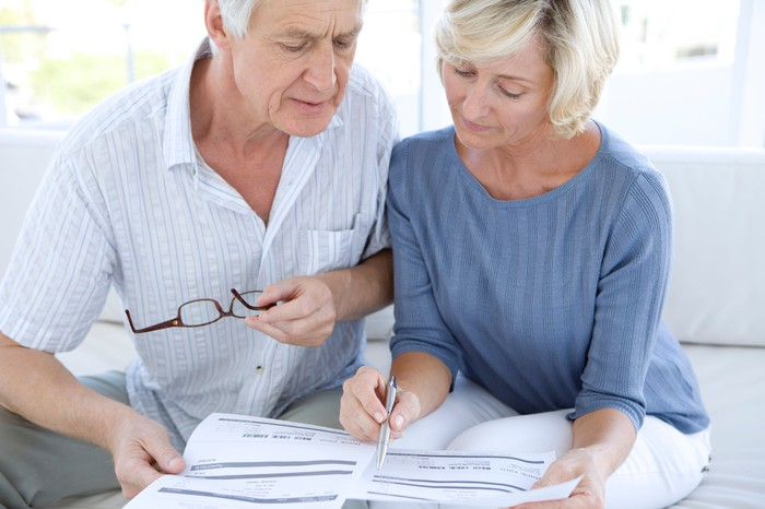 Senior couple looking at paperwork with concerned expressions.