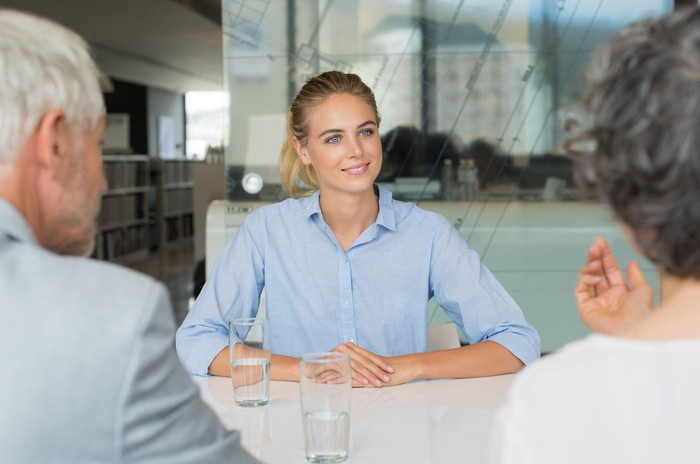 Woman in collared shirt sitting across from male and female