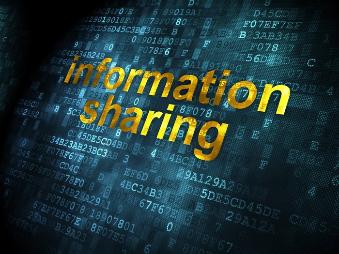 The words information sharing surrounded by digital code.