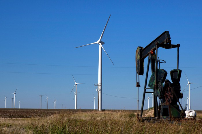 An oil rig and a wind turbine in a field.