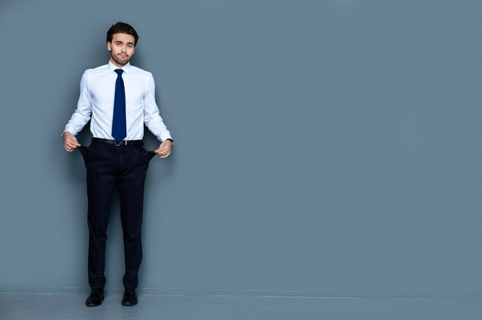 Man in white shirt, blue tie, black pants holding his pockets out to show that they are empty.