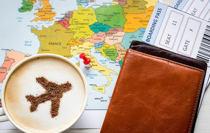 A coffee cup with a plane drawn in the foam of the coffee sits on a map next to some travel documents.