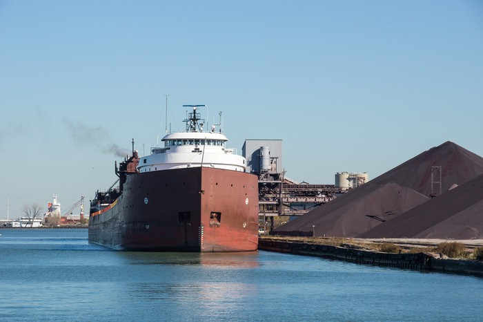 Dry bulk ship next to pile of coal