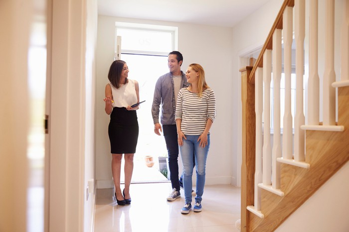 Professionally dressed woman shows a couple around a home