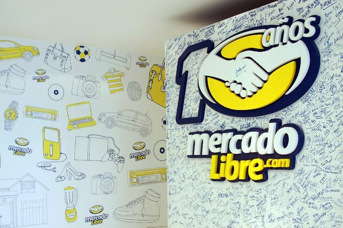 A wall with the MercadoLibre log and employee signatures.