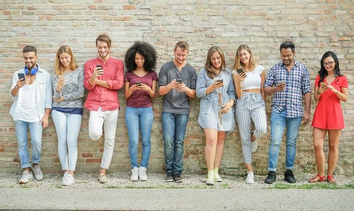 Group of Millennials browsing smartphones.