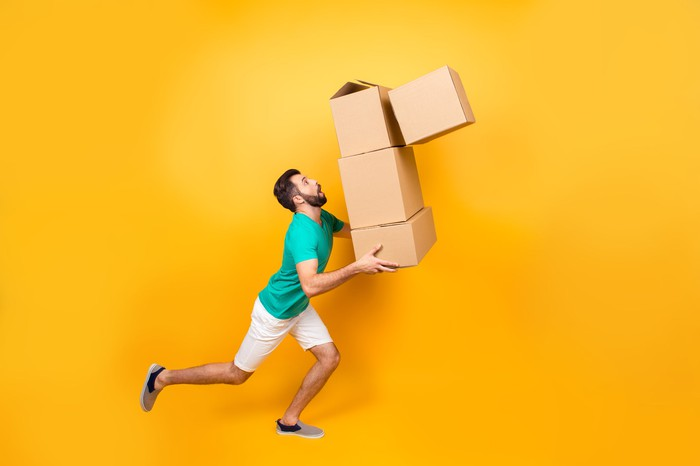 Man carrying toppling boxes