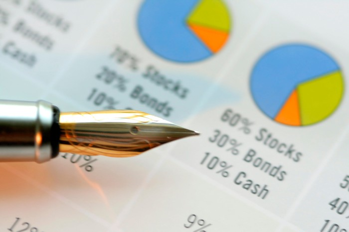 A fountain pen pointing to an asset allocation pie chart showing a majority of assets in stocks