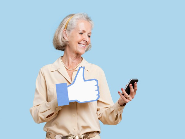 mature woman facebook like thumbs up getty