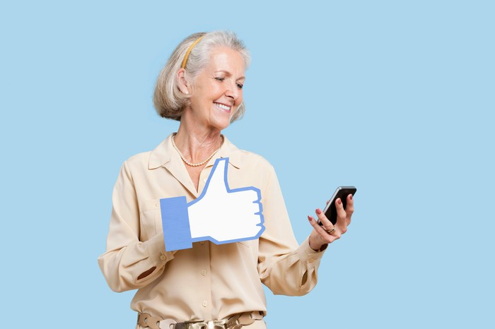 A woman with a Facebook thumbs up icon while using her mobile phone.