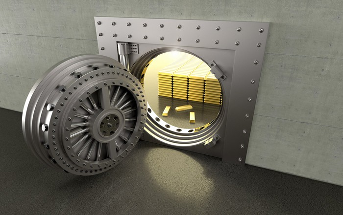 A bank vault with the door open showing the gold bars inside.