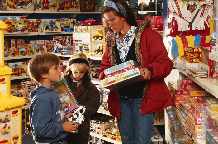 Woman shopping in toy store with boy and girl.