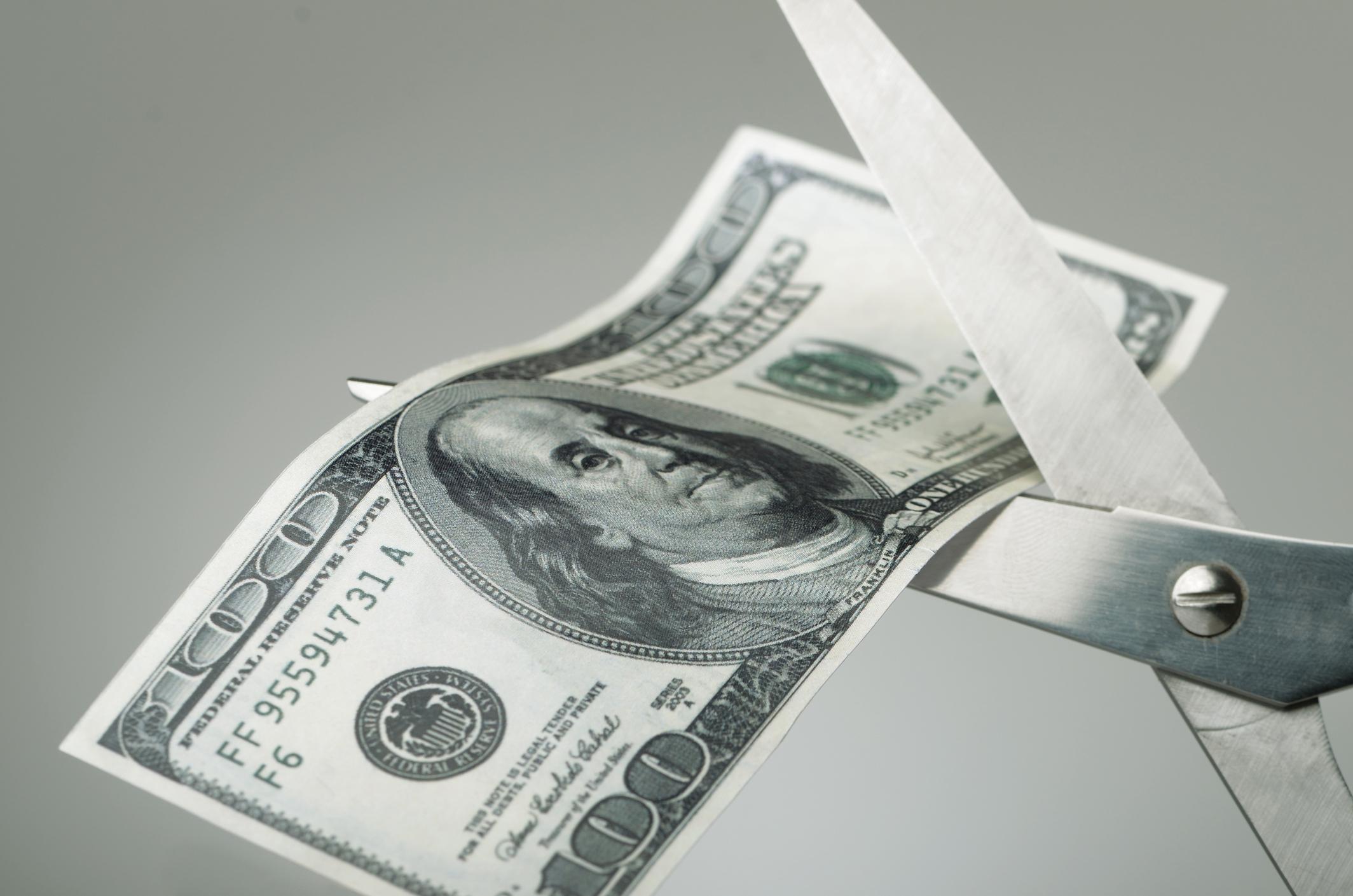 Pair of scissors cutting a $100 bill