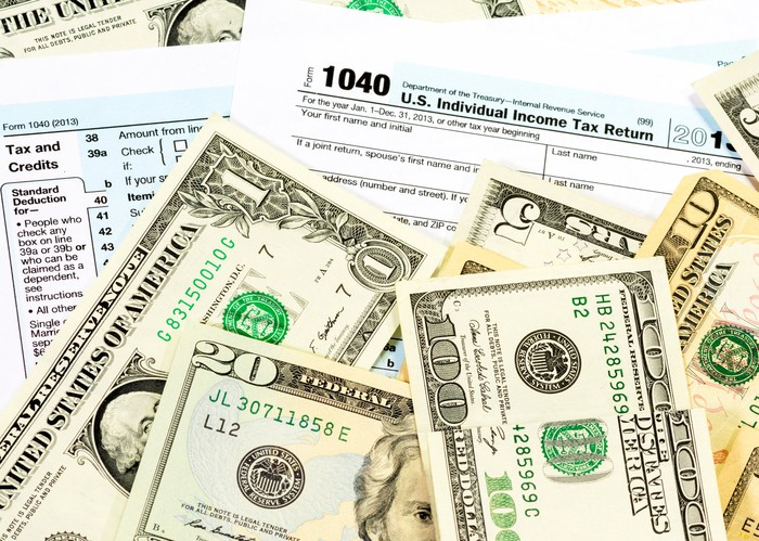 Money scattered on top of IRS tax forms.