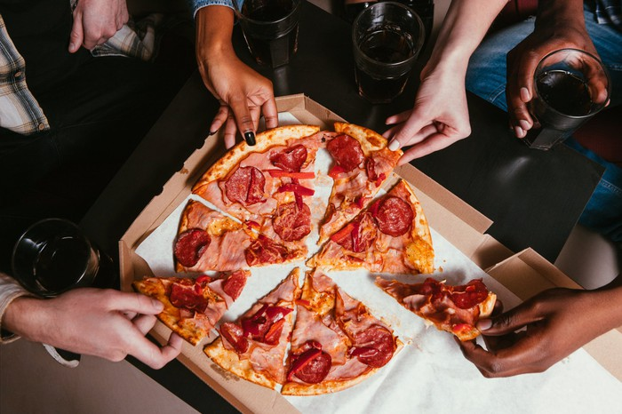 Four hands pulling slices of pizza from a pizza box