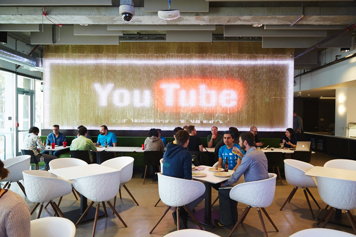 Google employees eating at the company's YouTube cafe with a large YouTube Logo in the background
