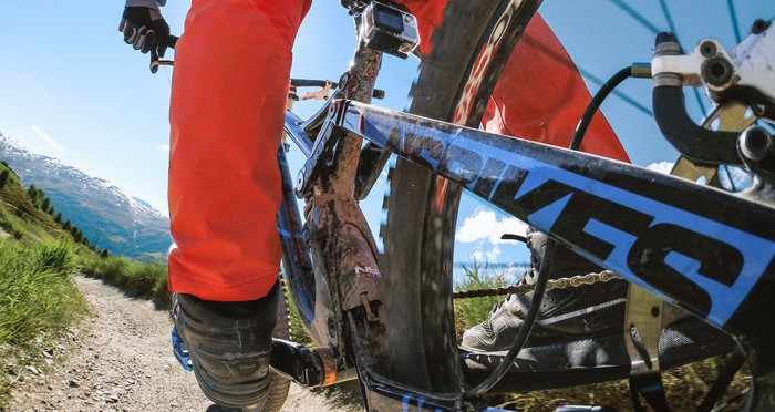 View from GoPro camera on the left rear wheel of a mountain bike on a rock path on a clear day.