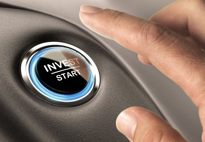 A finger about to press a button labeled invest/start.