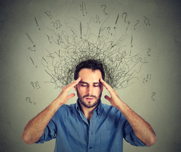 Man with hands to head, with question marks and exclamation points coming out of his head