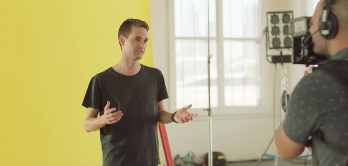 Snap CEO Evan Spiegel stands in front of a yellow background and explains the updated Snapchat design while being filmed by a cameraman