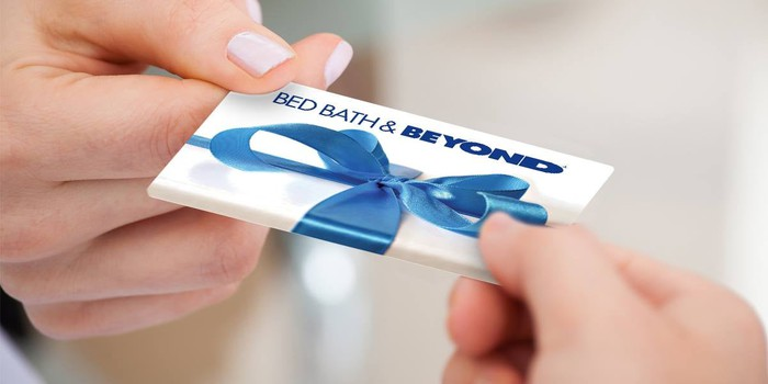 A hand giving a blue-and-white Bed Bath & Beyond gift card to another hand