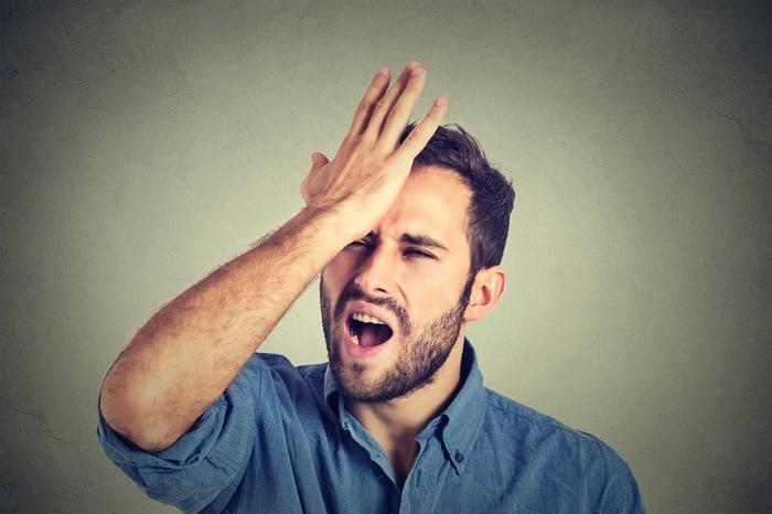 A man slaps himself on his head.
