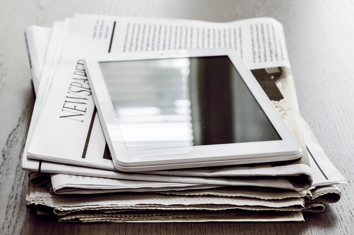 A tablet sitting on top of some newspapers.