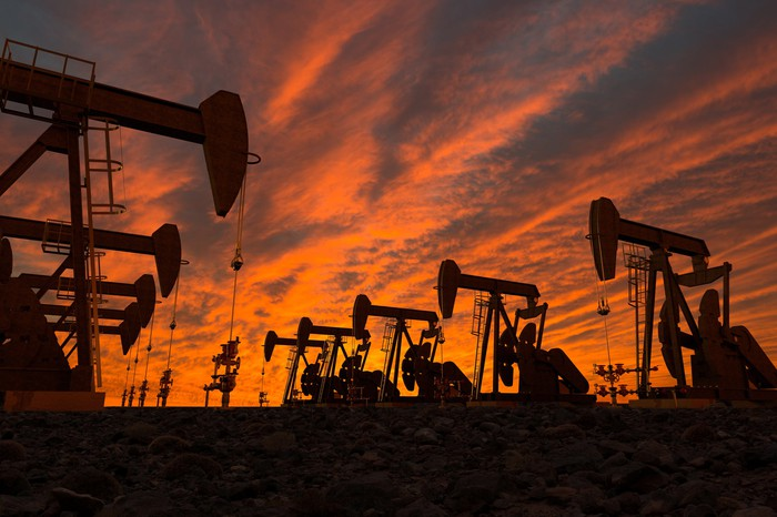 The silhouettes of oil pumps with a red sky in the background.
