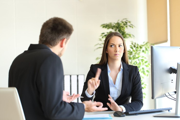 A woman looks stern in conversation with a man.