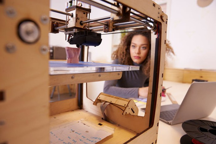 A woman on a laptop looking at a design in a 3D printer.