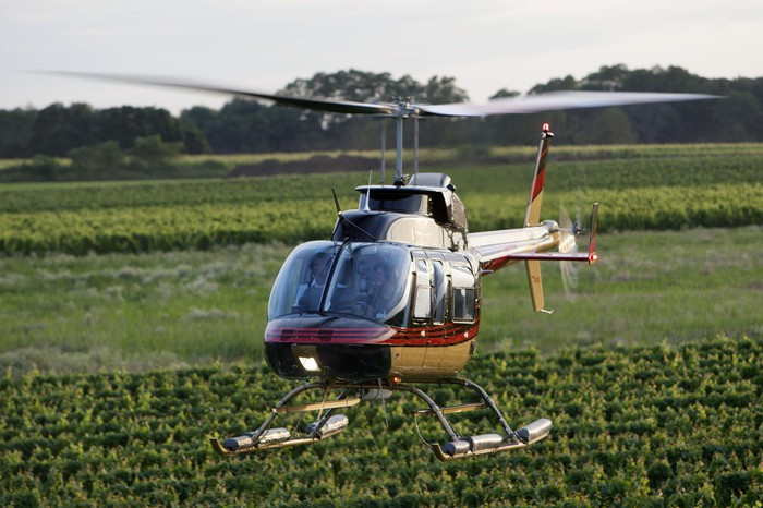 A maroon, gold, and black Bell helicopter flying low over farmland.