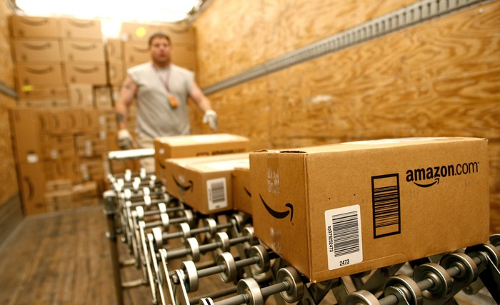 Amazon packages on a conveyer belt with a warehouse worker in the background
