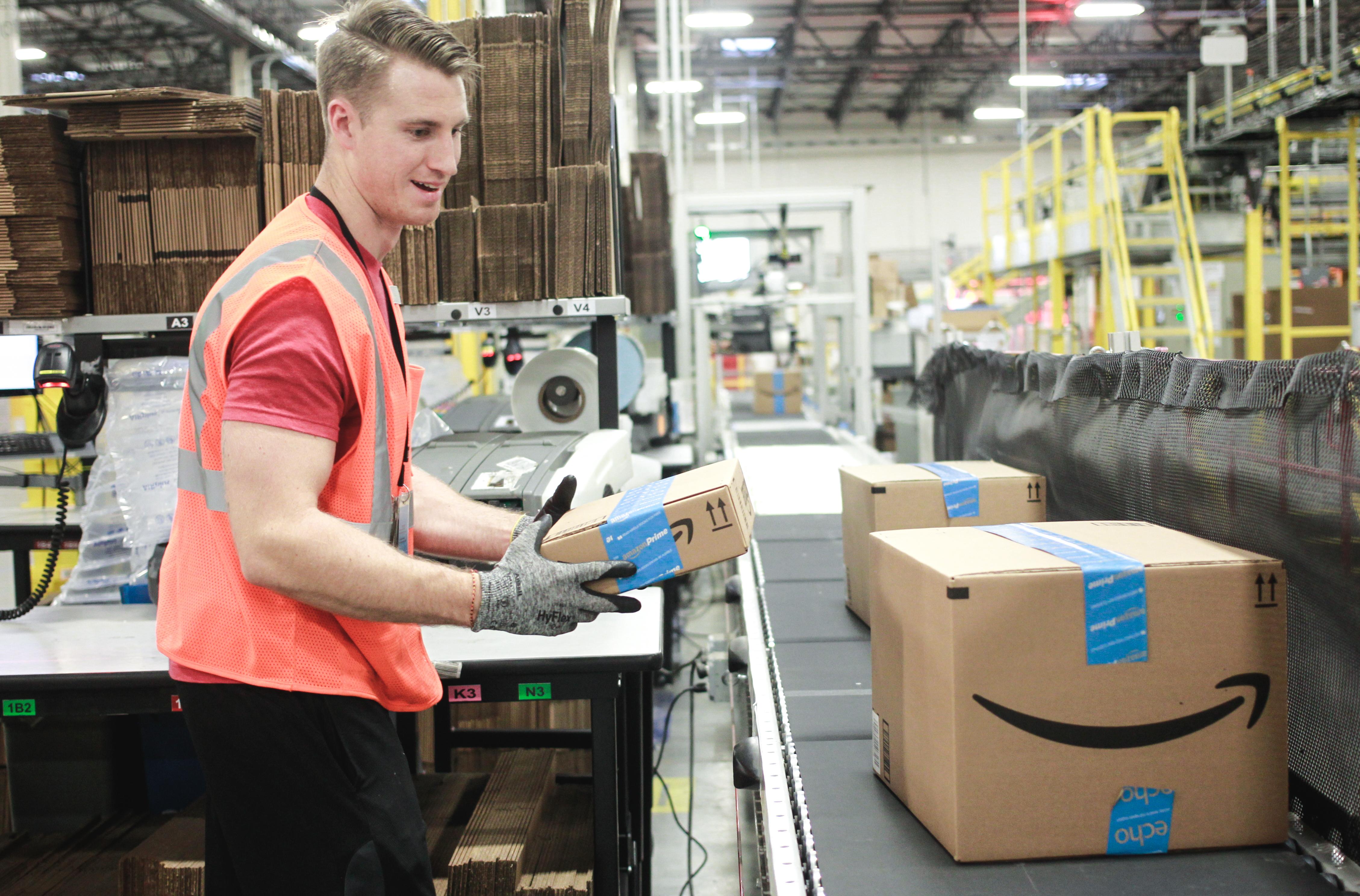 Man placing Amazon box on a conveyor belt.