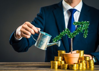 Investment - businessman watering plant shaped like high yield arrow