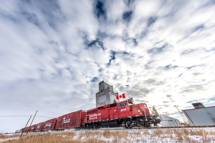 A red Canadian Pacific locomotive running on a track under white clouds.