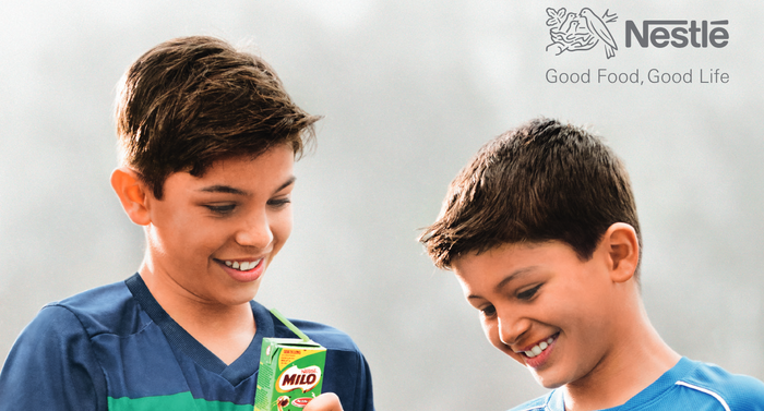 Two children with one holding a Milo box, with the Nestle logo and slogan at upper right.